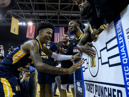 Murray State's Ja Morant (12) puts a Racers sticker on the NCAA tournament ticket board following the team's win over Belmont in an NCAA college basketball game for the Ohio Valley Conference men's tournament championship in Evansville, Ind., Saturday, March 9, 2019. (Sam Owens/Evansville Courier & Press via AP)