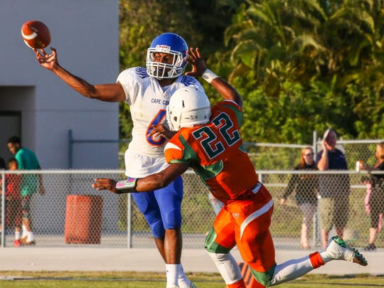 Cape Coral Maurice Flournoy gets rid of the pass just as Dunbar's Lajuan Preston closes in. Cape Coral played Dunbar High in their spring football game, Friday, May 27, 2016.