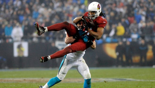 Arizona Cardinals wide receiver Larry Fitzgerald (11) catches a pass over Carolina Panthers middle linebacker Luke Kuechly (59) during the fourth quarter in the 2014 NFC Wild Card playoff football game at Bank of America Stadium.