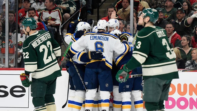 The St. Louis Blues celebrate a goal while two Wild players skate past during the first period in Game 5 on Saturday.