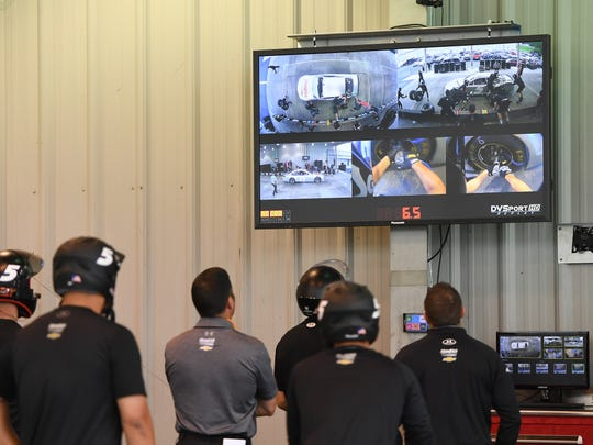 The pit crew for NASCAR Sprint Cup series driver Kasey Kahne watches video from their practice at Hendrick Motor Sports this summer.