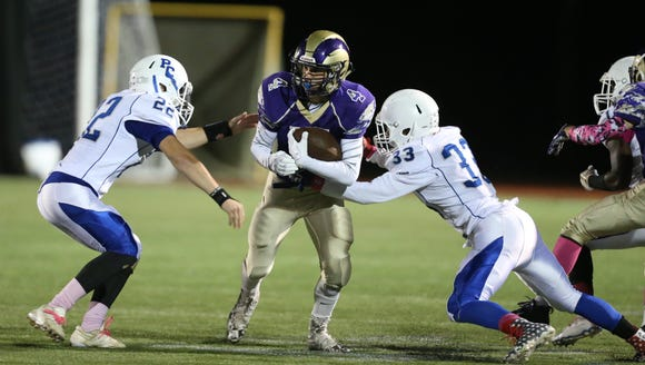 Clarkstown North's Eric Maurer (4) is tackles by Port