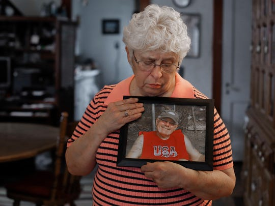 Kay Taynor holds a photo of her late husband, Gary, in Toledo, Ohio. Dozens of patients from a now-closed memory loss clinic in Ohio say its director told them they had Alzheimer's disease when they really didn't.