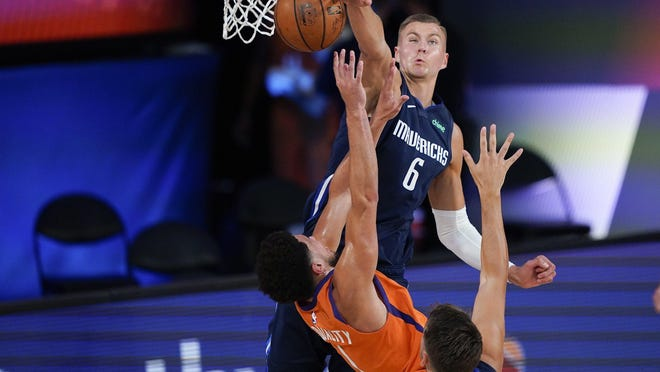 The Mavericks' Kristaps Porzingis blocks a shot by the Suns' Devin Booker on Sunday.