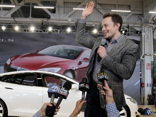 Tesla CEO Elon Musk waves during a 2012 rally at the Tesla factory in Fremont, Calif. Unlike Solyndra, the California-based solar company backed by federal loan guarantees that filed for bankruptcy, Tesla Motors has flourished, paying back a $465 million loan nearly 10 years early.