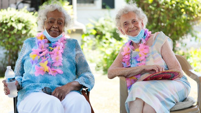 """Opal Walker, left, 94, with her friend Dollene Scott, 97, sit together at the latter's home July 29. The two are the last two surviving members of """"The Posse,"""" a group of Black women who all lived near each other and have served as community leaders in their Hilltop neighborhood."""