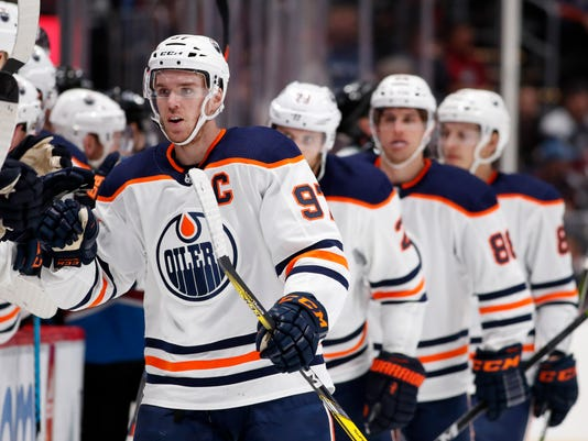 Edmonton Oilers center Connor McDavid, front, is congratulated as he passes the team box after scoring his first of two goals in the third period of an NHL hockey game against the Colorado Avalanche, Sunday, Feb. 18, 2018, in Denver. (AP Photo/David Zalubowski)