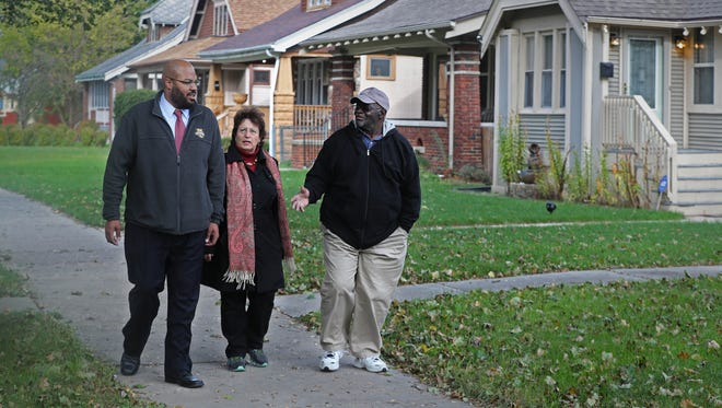 (From left) The Rev. Will Davis of Invisible Reality Ministries, Toni Wagner of St. Catherine Catholic Church and Frank Finch III of Mt. Calvary Lutheran Church walk along one of the blocks in the Sherman Park neighborhood revitalized by Southeastern Wisconsin Common Ground. The three worked on the Common Ground campaign that forced lenders to reinvest in the community where some blocks were all but decimated in the foreclosure crisis.