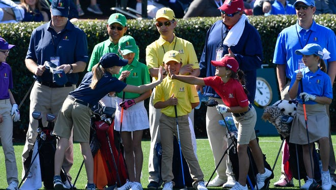Naples' Jensi Krampel (right) high-fives another player as girls in the 7-9 age group congratulate each other during the finals of the Drive, Chip & Putt competition at Augusta National Golf Club on Sunday. (Michael Madrid/USA TODAY Sports)