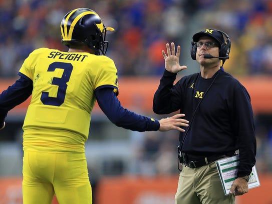 Michigan quarterback Wilton Speight talks with head