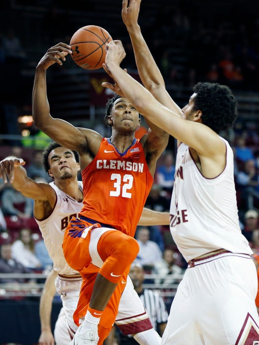 Clemson's Donte Grantham (32) shoots between Boston College's Jerome Robinson, left, and Johncarlos Reyes during the first half of an NCAA college basketball game in Boston, Wednesday, Jan. 3, 2018. (AP Photo/Michael Dwyer)
