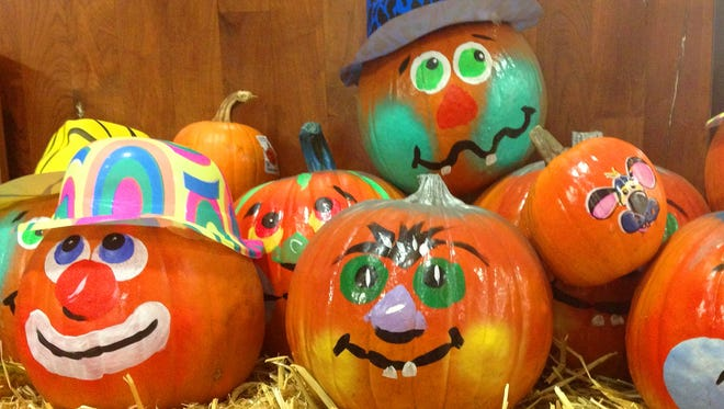 Decorated pumpkins on hay for Halloween.