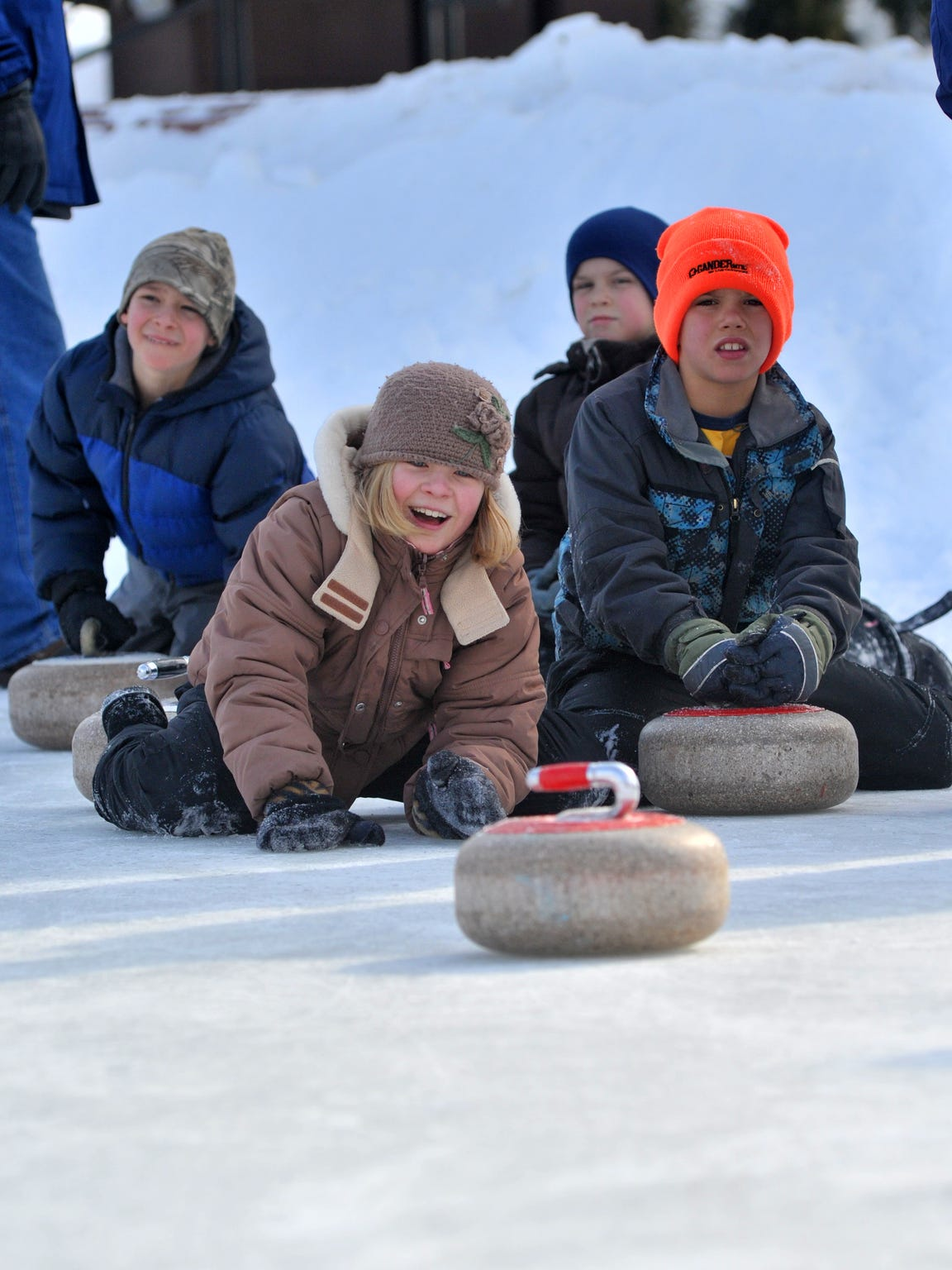 Claire Butalla of Wausau tries curling while her cousin Jake Pease of Marathon looks on at The 400 Block in downtown Wausau at the 2014 Winter Fest.