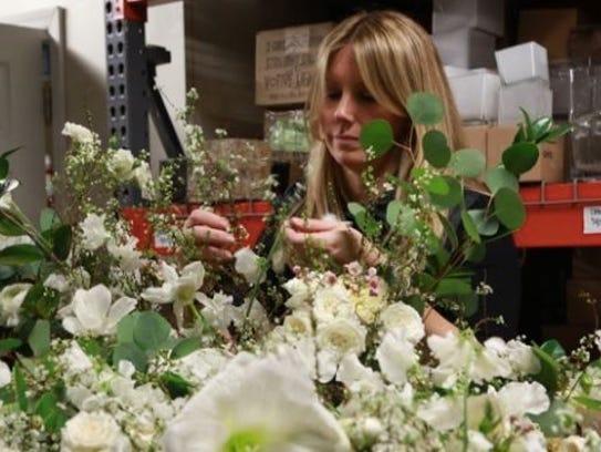 Grove arranges flowers into small bundles.