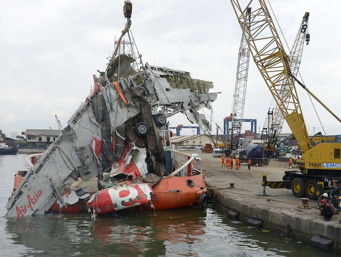 A crane is used to lift the fuselage of the crashed