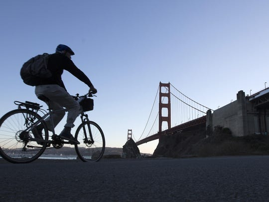 A cyclist rides along a paved road in Fort Baker near Lime Point in the Golden Gate National Recreation Area in San Francisco.