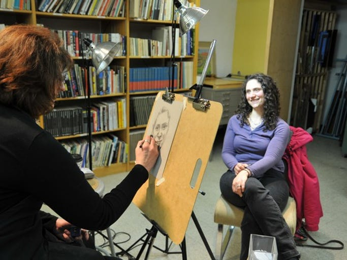 Heather Mastromarco has her portrait done by artist Suzann Beck during the Downtown St. Cloud Art Crawl on Friday, March 21, at the Paramount.