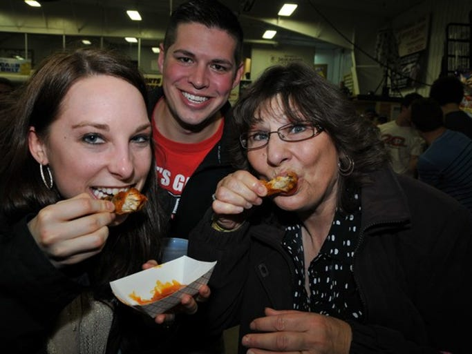 Amber Sarder, Jeremy Sarder and Debbie Tischmak enjoy wings during Wingfest 2014 on Saturday, April 5, at the Sports Arena East Building at the Benton County Fairgrounds in Sauk Rapids.