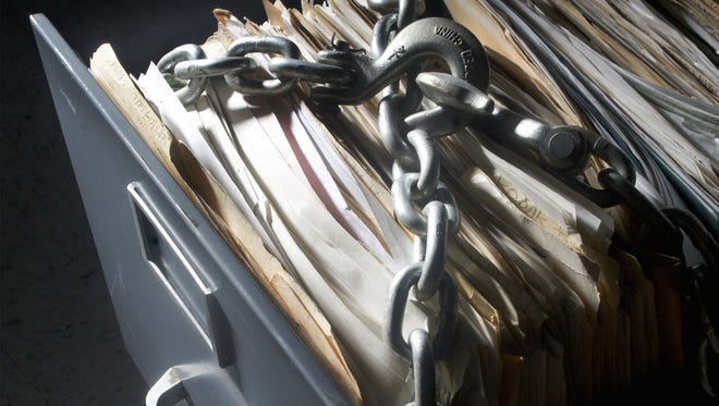 Photo-illustration of a file cabinet that is chained shut
