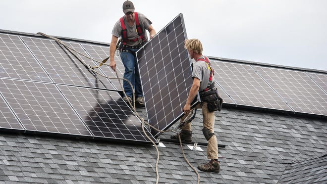 Brennan Scott, left, and David Strippe of SunCommon install solar panels on a house in Shelburne on Wednesday, August 31, 2016.
