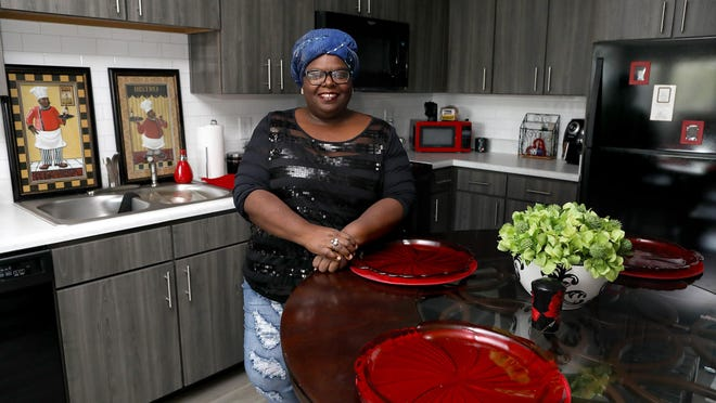 Marie Gaddy stands in her new kitchen at the newly constructed The Grove at Sweetwater Preserve in Gainesville. The development is replacing the Woodland Park housing development for low-income residents that was built in 1970.