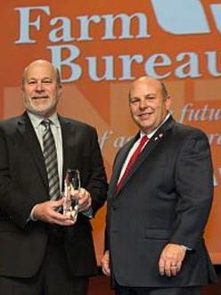 American Farm Bureau Federation President Zippy Duvall (right) presents the AFBF's highest honors, the Distinguished Service Award to former president Bob Stallman during the national convention in Phoenix.