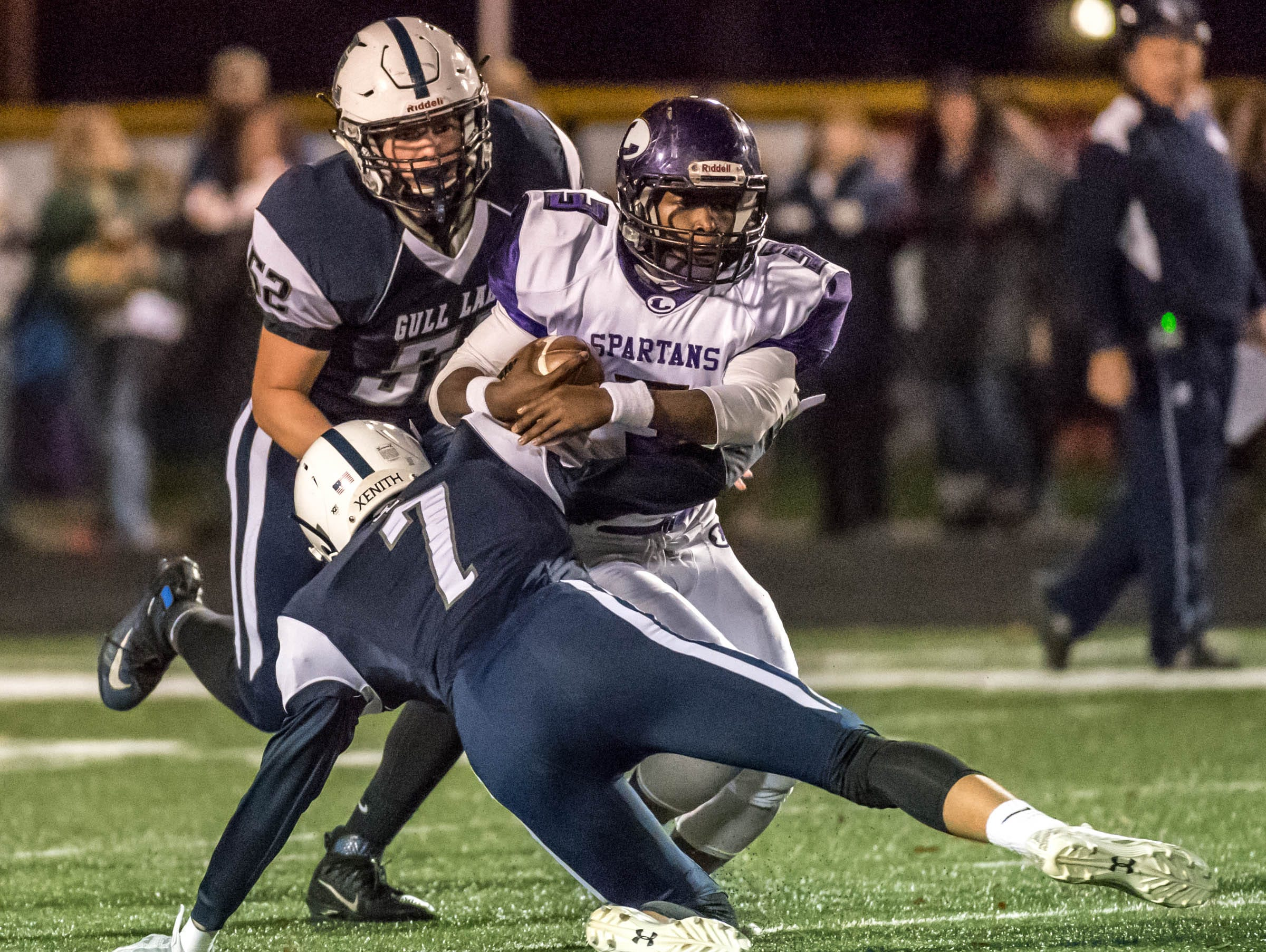 Gull Lake's Ryan McMullen (7) and Avery Eastman (52) bring down Lakeview's JayVion Settles (3) during first half action Friday evening.