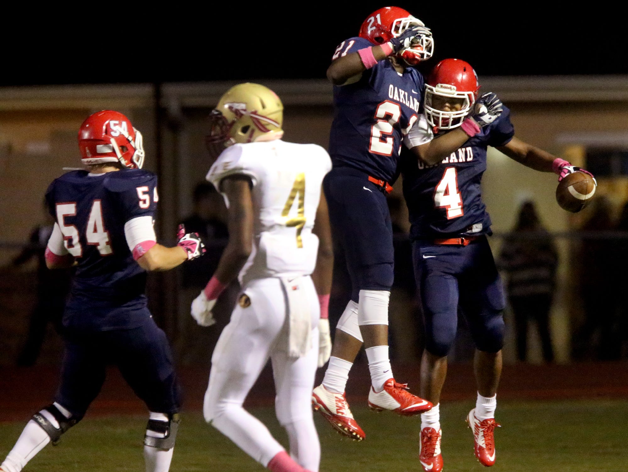 Oakland's Justice Dingle (21) and Lazarius Patterson (4) celebrate Oakland's first touchdown of the game against Riverdale at Oakland.