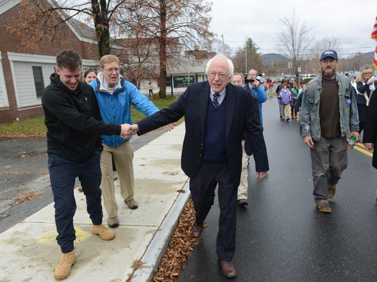 Presidential candidate Bernie Sanders shakes hands with people as he marches in the Veterans Day Parade on Nov. 11, in Lebanon, N.H.