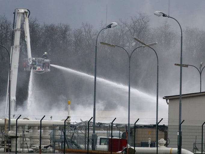 A firefighter sprays water after an explosion at a