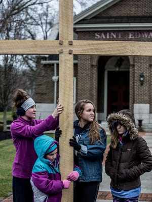 Eowyn Frail, 16, Gwen Koske, 7, Bekka Daw, 16 and Sarah Daw, 13, stand with the cross in front of St. Edwards in Granville as scripture is read. The youth along with community members from local churches carried the cross through Granville for Good Friday.