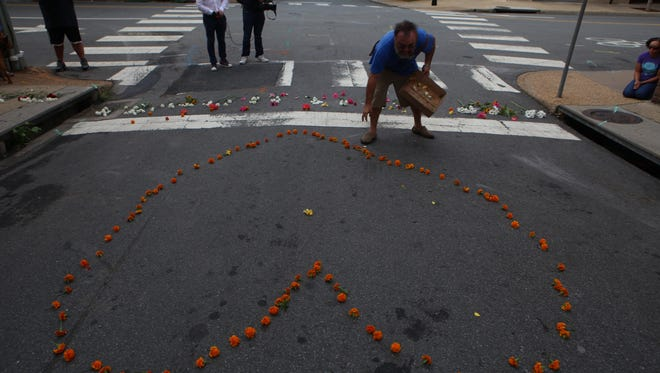 David Heins spreads flowers in the shape of a heart on Sunday in Charlottesville, Va., a day after one person died in violent protests when white supremacists clashed with counter protesters.