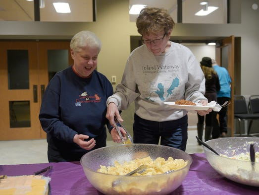 Marlene Morlock of Davisburg (right) helps Stella Vandervennet
