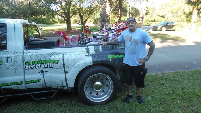 John Garappolo, owner of Inzane Tattoo, delivers 11 bicycles and lots of toys, clothing and gifts for children at the Hibiscus Children's Center in St. Lucie County to make their holiday season bright.