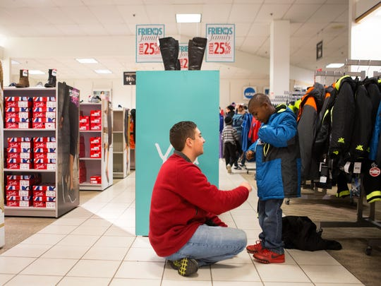 Michael Surtel of Pittsford helps Messiah Williams, 6, pick out a coat as part of the Salvation Army's Project Bundle Up.