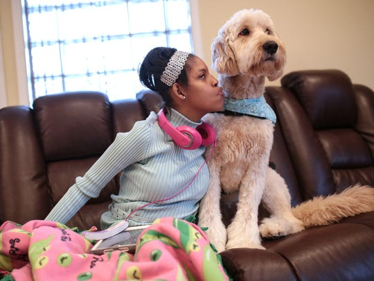 Kiara Williamson, 23, sits with her service dog Diego at her home on March 30, 2017 in Southfield, Mich. Williamson, who has Cri du chat syndrome and seizure disorder, uses a medical alert dog to help her with tasks and alert her mother when she is having seizures.