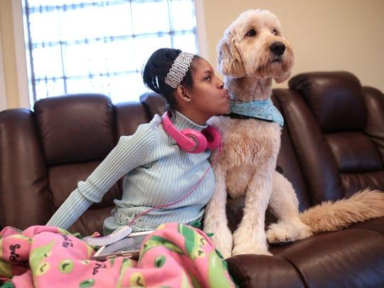 Kiara Williamson, 23, sits with her service dog Diego