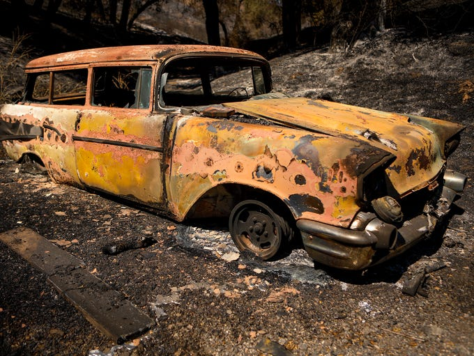 A burned out car sits on Stagecoach Canyon Road after