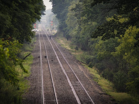 Police searched a wooded area near the railroad tracks