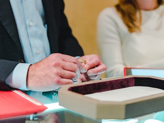 Christie's auction house specialists evaluate a ring.