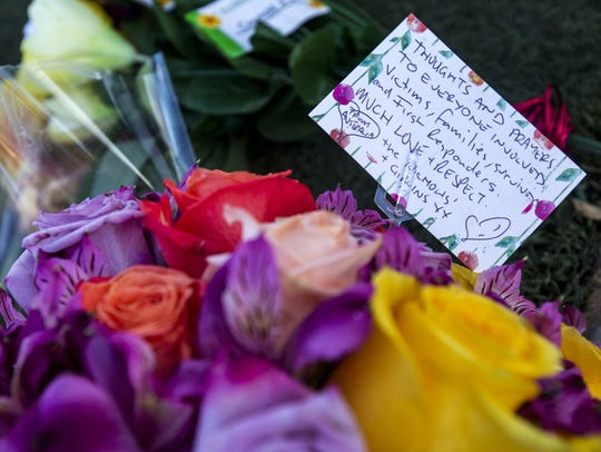A note on a bouquet of flowers is pictured at a memorial