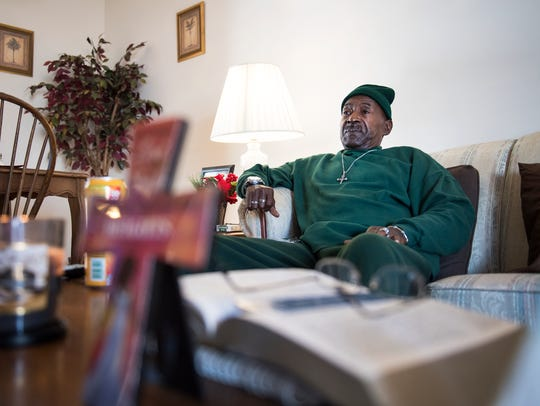 Fred Barksdale watches television in his home in Greenville
