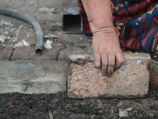 Margarita Armijo lays bricks to rebuild the floor of
