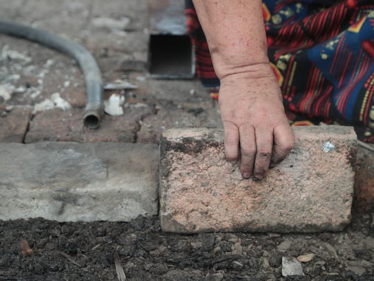 Margarita Armijo lays bricks to rebuild the floor of her home which burned down on the Torres-Martinez Reservation, July 31, 2018.