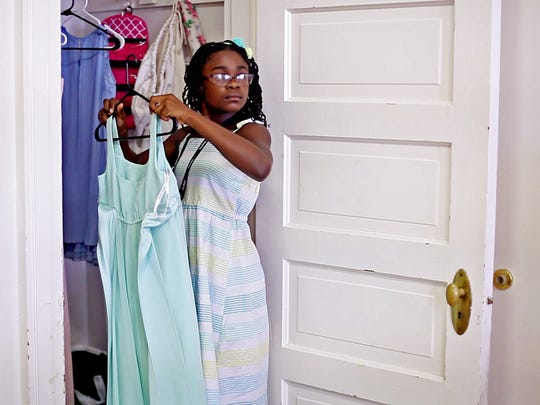 Kearston Gonzales, 11, of Hampton puts away preformance dresses on arrival day for participants in HeifetzPEG, or Program for the Exceptionally Gifted, on Thursday, July 14, 2016 at Mary Baldwin College. The PEG students, aged 8 to 13, come from all over the country and have to apply and do a video audition before being accepted into the three-week stringed instrument program.