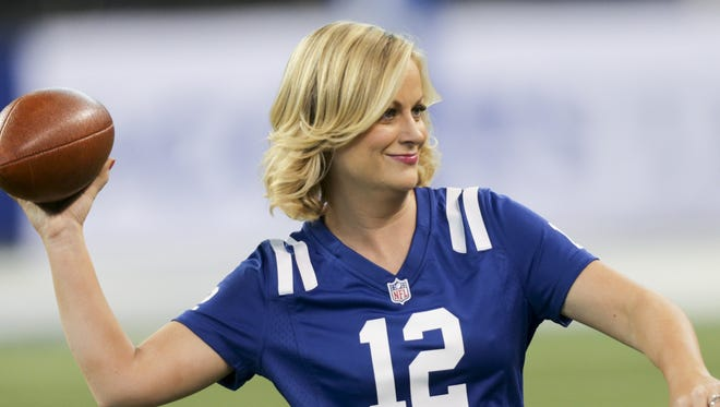 """Amy Poehler practices her passing during a 2013 visit by """"Parks and Recreation"""" to Lucas Oil Stadium."""