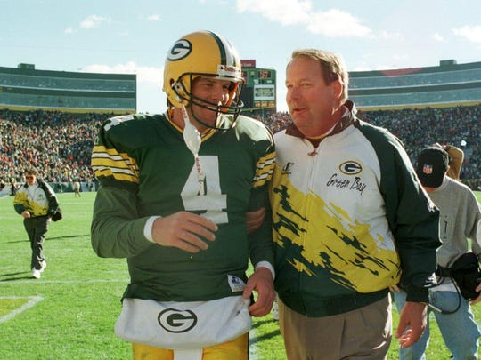 Mike Holmgren and Brett Favre walk off the field after a win over the Lions in 1995.