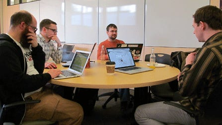 Alan Palazzolo, left, Andrew Dahl, Bill Bushey and Jake Dalton collaborate on analyzing government data at the monthly meetup of Open Twin Cities in Minneapolis.