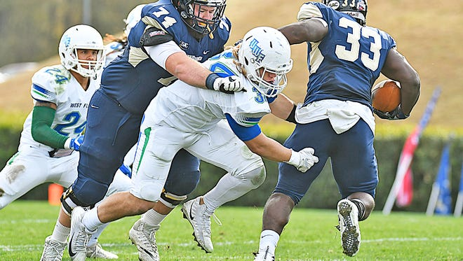 University of West Florida defensive lineman Austin Dukes tackles Wingate running back Blake Hayes on Saturday in Wingate, North Carolina.