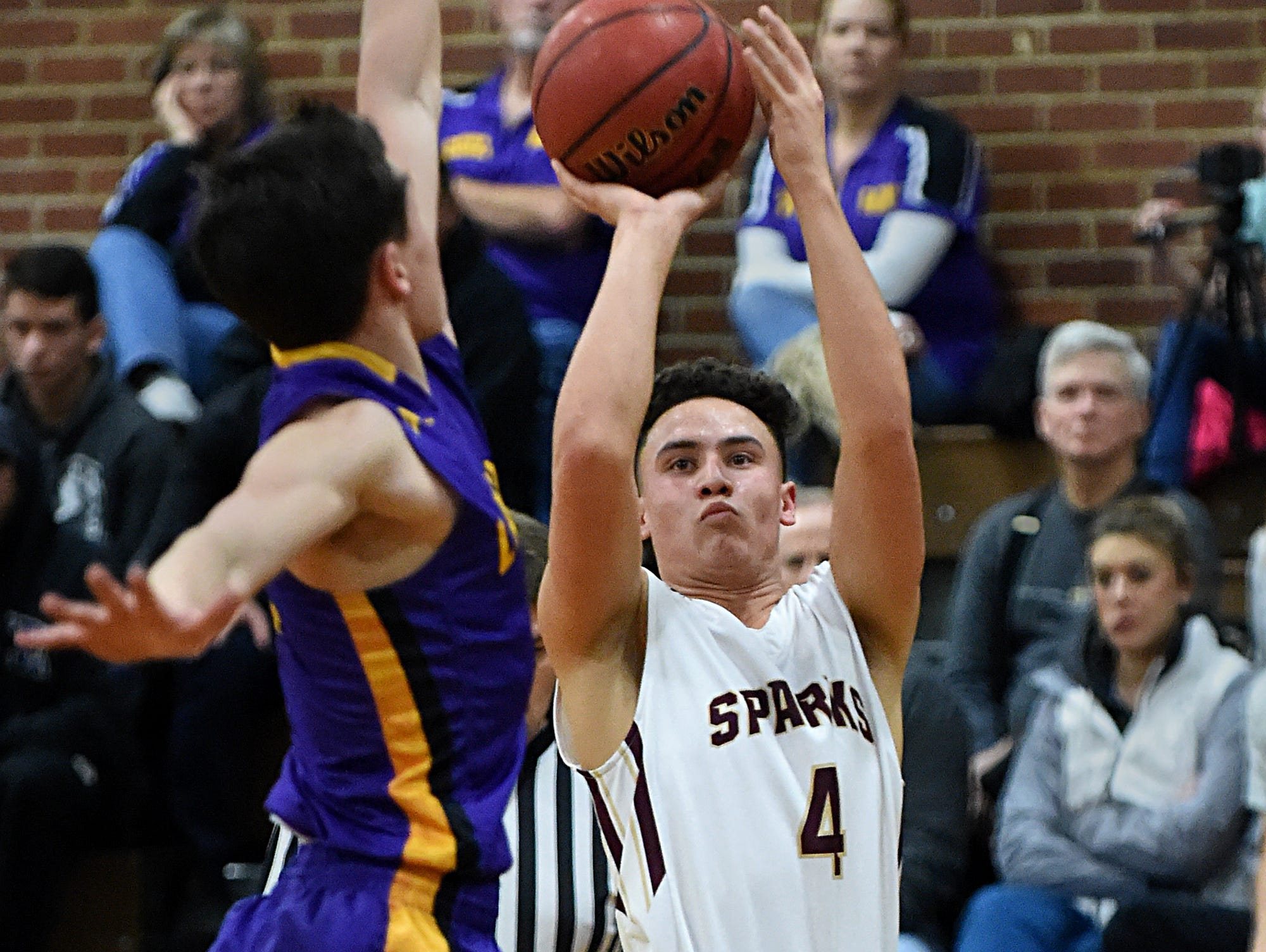 Sparks's James Bates shoots with Lassen's Kevin Barnetche looking to block during Tuesday's game at Sparks.